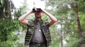 exército : hunting, war, army and people concept - young soldier, ranger or hunter with binocular observing forest