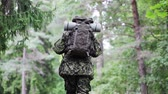 exército : war, hiking, army and people concept - young soldier, ranger or hunter with backpack walking in forest
