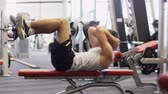 práce : sport, bodybuilding, lifestyle and people concept - young man making abdominal exercises in gym