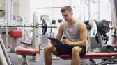 aplicativo : sport, bodybuilding, lifestyle, technology and people concept - young man with tablet pc computer in gym