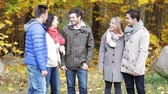 pretty : season, friendship, drinks and people concept - group of smiling men and women talking in autumn park