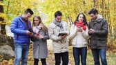 гаджет : season, people, technology and friendship concept - group of smiling friends with smartphones and tablet pc computers in autumn park Стоковые видеозаписи