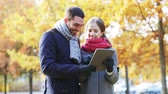 pretty : technology, relationship, family and people concept - smiling couple with tablet pc computer in autumn park Stock Footage