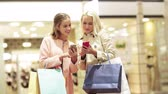 sale, consumerism, technology and people concept - happy young women with smartphones and shopping bags talking in mall