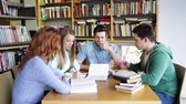 literatura : people, knowledge, education and school concept - group of students reading books and preparing to exam in library