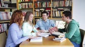 university : people, knowledge, education and school concept - group of happy students reading books and preparing to exam in library Stock Footage