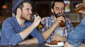 saúde : people leisure friendship and celebration concept  happy male friends drinking beer eating bread snack and clinking glasses at bar or pub Vídeos