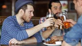 quadrilha : people leisure friendship and celebration concept  happy male friends drinking beer eating bread snack and clinking glasses at bar or pub Vídeos