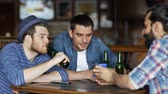 quadrilha : people men leisure friendship and technology concept  happy male friends with smartphones drinking bottle beer at bar or pub