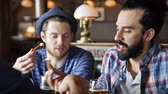 irlandês : people leisure friendship and communication concept  happy male friends drinking beer eating snacks and talking at bar or pub