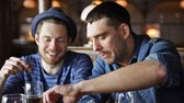 língua : people leisure friendship and communication concept  happy male friends drinking beer eating snacks and talking at bar or pub