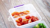 ervilha : food storage dieting and people concept  close up of woman opening container or plastic box with vegetables at home kitchen