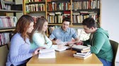 grupa : people knowledge education and school concept  group of happy students reading books and preparing to exam in library Wideo