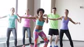 instrutor : fitness sport dance and lifestyle concept  group of smiling people with coach dancing zumba in gym or studio Stock Footage