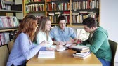 střední škola : people knowledge education and school concept  group of happy students reading books and preparing to exam in library Dostupné videozáznamy