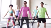 instrutor : fitness sport training gym and lifestyle concept  group of people exercising with bars in gym