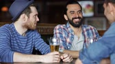 irlandês : people, men, leisure, friendship and communication concept - happy male friends drinking beer at bar or pub