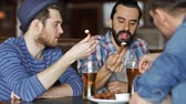 quadrilha : people, men, leisure, friendship and communication concept - happy male friends drinking beer and eating bread snack a at bar or pub