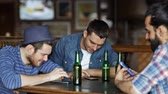 quadrilha : people, men, leisure, friendship and technology concept - happy male friends with smartphones drinking bottle beer at bar or pub