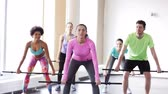 instrutor : fitness, sport, training, gym and lifestyle concept - group of people exercising with bars in gym