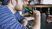 алкоголь : people, men, leisure, friendship and technology concept - happy male friends with smartphones drinking bottle beer at bar or pub