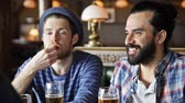 irlandês : people, leisure, friendship and communication concept - happy male friends drinking beer, eating snacks and talking at bar or pub