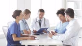 grupa : hospital, profession, people and medicine concept - group of happy doctors with clipboard meeting and discussing something at medical office Wideo