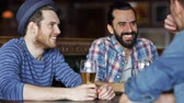 sedento : people, men, leisure, friendship and communication concept - happy male friends drinking beer at bar or pub