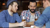 quadrilha : people, leisure, friendship and celebration concept - happy male friends drinking beer, eating bread snack and clinking glasses at bar or pub