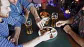 жареный : people, men, leisure, friendship and communication concept - happy male friends drinking beer and eating snacks a at bar or pub