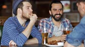 жареный : people, men, leisure, friendship and communication concept - happy male friends drinking beer and eating bread snack a at bar or pub