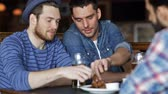 alho : people, men, leisure, friendship and communication concept - happy male friends drinking beer and eating bread snack a at bar or pub