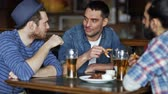 foods : people, men, leisure, friendship and communication concept - happy male friends drinking beer and eating tasty snacks a at bar or pub Stock Footage