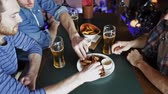 molho : people, men, leisure, friendship and communication concept - happy male friends drinking beer and eating snacks a at bar or pub