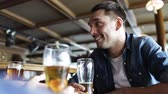 língua : people, men, leisure, friendship and communication concept - happy male friends drinking beer at bar or pub