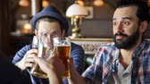 hat : people, leisure, friendship and celebration concept - happy male friends drinking beer, eating snacks and clinking glasses at bar or pub Stock Footage