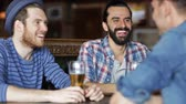 quadrilha : people, men, leisure, friendship and communication concept - happy male friends drinking beer at bar or pub