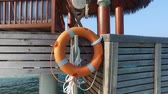 doca : travel, tourism, safety, vacation and summer holidays concept - lifebuoy hanging on beach patio or terrace in sea water Stock Footage