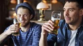people, toast, leisure, friendship and celebration concept - happy male friends drinking beer and clinking glasses at bar or pub Stock Footage
