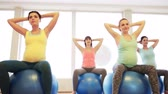 гимнастика : pregnancy, sport, fitness, people and healthy lifestyle concept - group of happy pregnant women exercising on ball in gym
