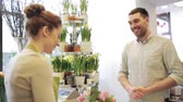 buquê : people, shopping, sale, floristry and consumerism concept - happy florist woman wrapping flowers in paper and man at flower shop Stock Footage