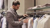 cabide : sale, shopping, fashion, style and people concept - elegant young man in suit choosing clothes in mall or clothing store