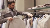 armário : sale, shopping, fashion, style and people concept - elegant young man in suit choosing clothes in mall or clothing store