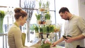 kupující : people, shopping, sale, floristry and consumerism concept - happy florist woman counting bunch cost at cashbox and man with credit card paying for purchase at flower shop Dostupné videozáznamy
