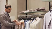 shopaholic : sale, shopping, fashion, style and people concept - elegant young man in suit choosing clothes in mall or clothing store