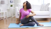 odchudzanie : fitness, sport, yoga, training and people concept - happy african woman exercising on mat at home
