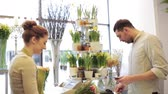 florista : people, shopping, sale, floristry and consumerism concept - happy florist woman counting bunch cost at cashbox and man with credit card paying for purchase at flower shop Vídeos