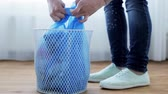 czystość : people, housework, cleaning and housekeeping concept - woman tying bag with garbage in waste bin at home