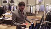 por cento : sale, shopping, fashion, style and people concept - elegant young man in suit choosing clothes with discount in mall or clothing store