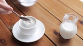 demitasse : unhealthy eating and drinks concept - hand with teaspoon pouring sugar into coffee cup on wooden table Stock Footage